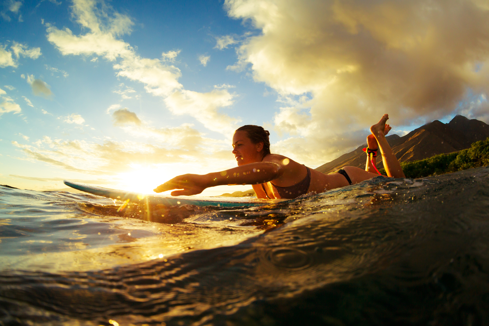 woman enjoying surfing in sunset